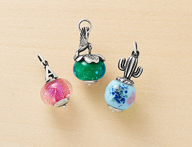 "Image features 3 art glass charms to show the different pairings of silver finials and art glass beads you can choose from. The first charm shown is the silver ""A"" Initial Finial paired with the Pink Glitter Art Glass Bead. The second charm is the silver Hummingbird Finial paired with the Sea Green Art Glass Bead. The third charm is the silver Cactus Finial paired with the Blue Abstract Art Glass Bead."