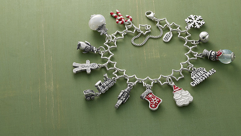 New sterling silver Star Charm Bracelet shown with an assortment of 12 Christmas-themed charms – featuring sterling silver, enamel and art glass designs.