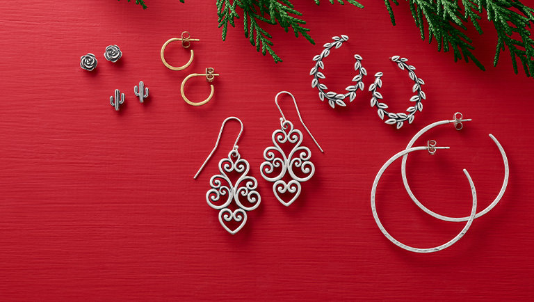 An assortment of earrings featuring small sterling stud earrings, dangling ear hooks, and a variety of hoop styles.