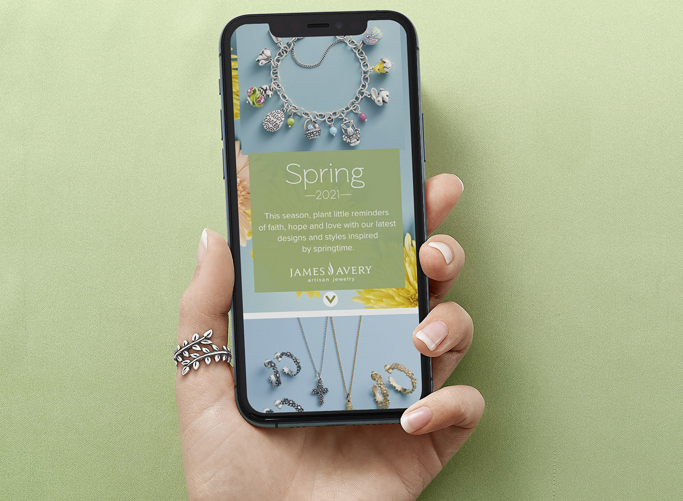 A hand holding a smartphone with an image of the new lookbook, featuring an assortment of designs for spring.