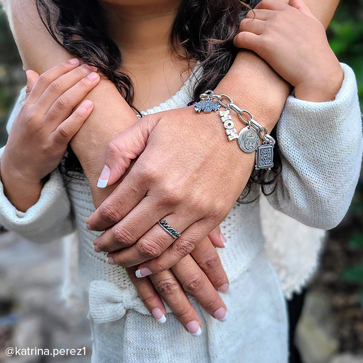 Mother wrapping her arms around her young daughter, wearing an assortment of mom-themed charms and a ring.