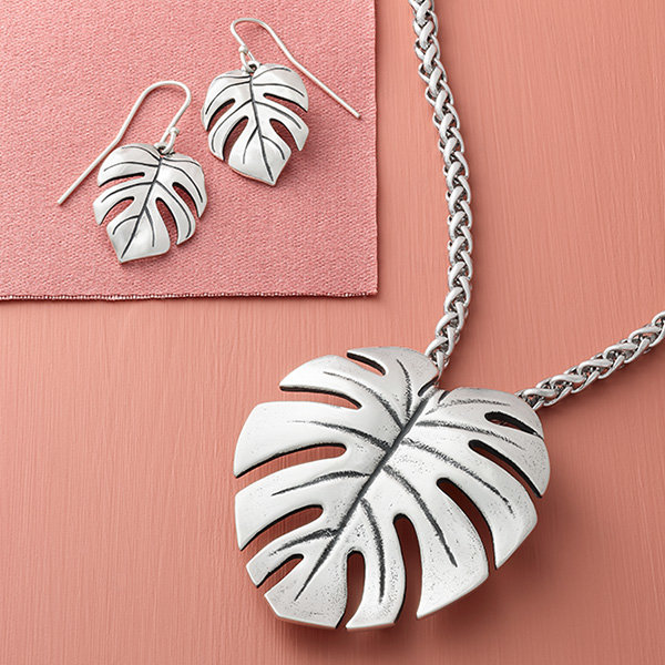 The sterling silver Monstera Leaf Pendant on a chain and the Monstera Leaf Ear Hooks.