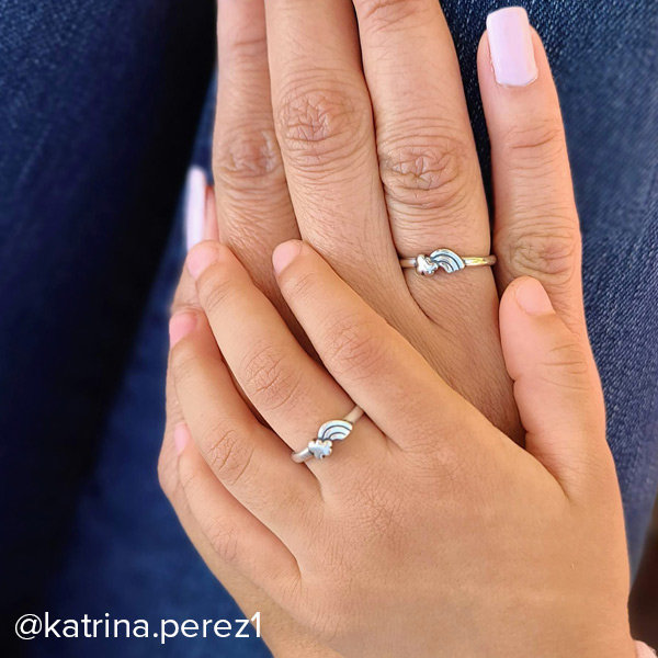 Hands of a woman and child wearing matching sterling silver Little Rainbow Rings.