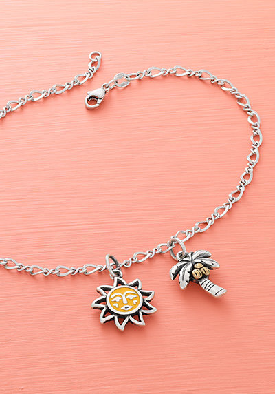 The sterling silver Medium Twist Ankle Bracelet with two summer-themed charms.