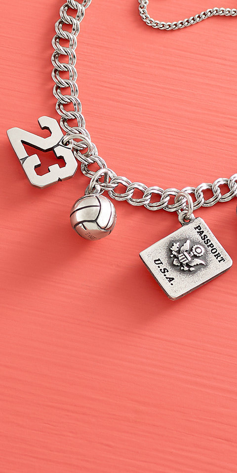 Two sport-themed charms and the Passport Charm on a charm bracelet.