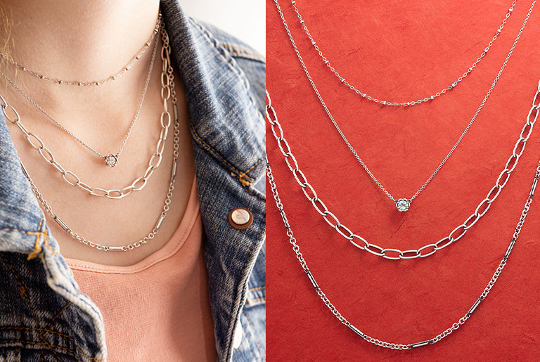 Woman wearing an assortment of chains and necklaces in a variety of lengths. A layered necklace look featuring two chains and two necklaces at different lengths.