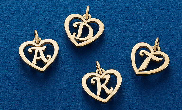 An assortment of 14K gold Heart Script Initial Charms, available in letters A-Z.